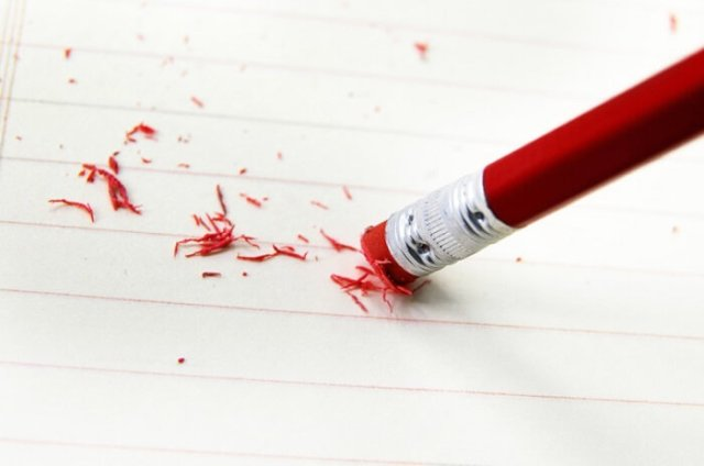 pen with red erased used on empty sheet of paper