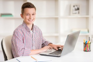 Boy sitting at desk with laptop and doing homework