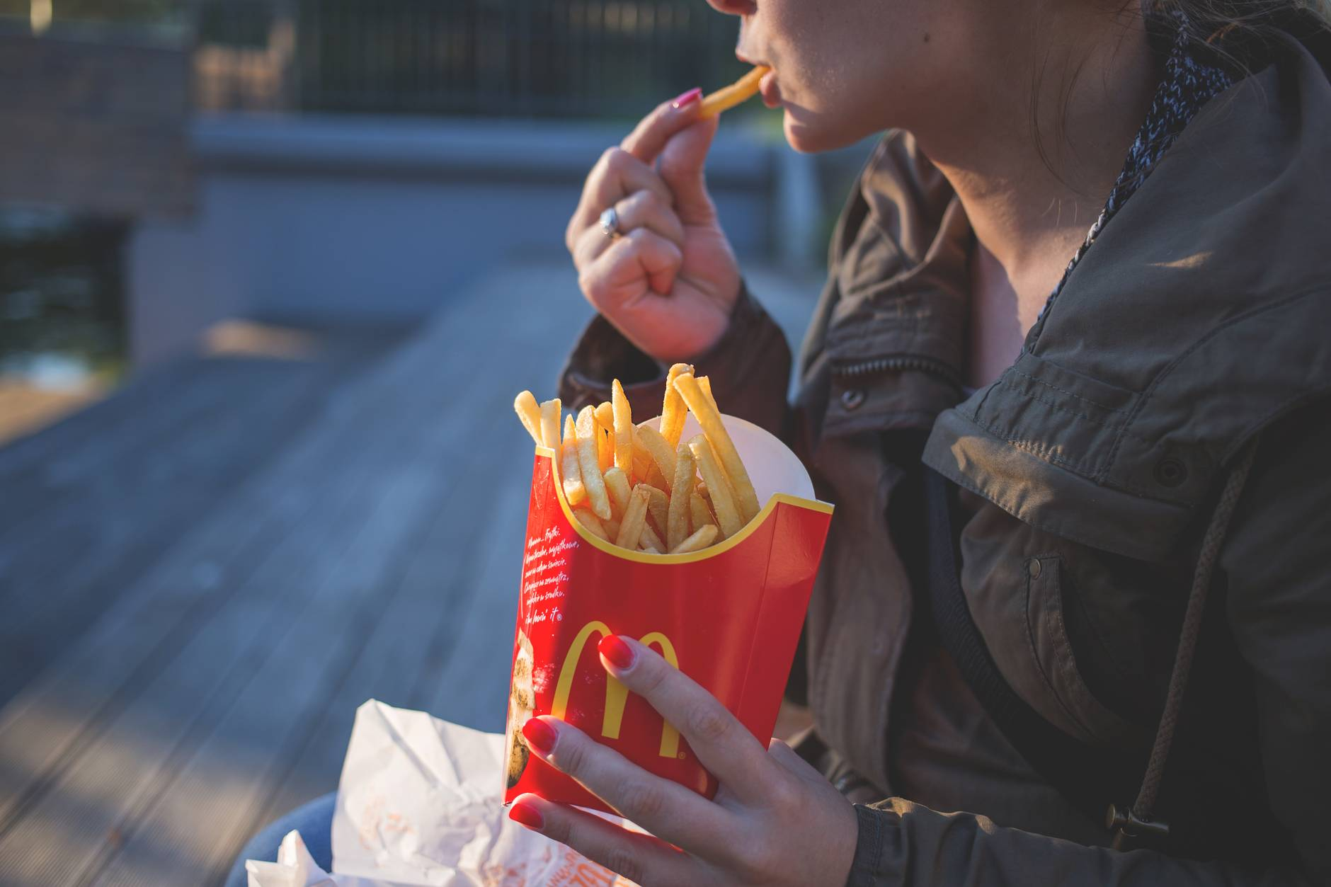 woman in brown classic trench coat eating mcdo fries during daytime