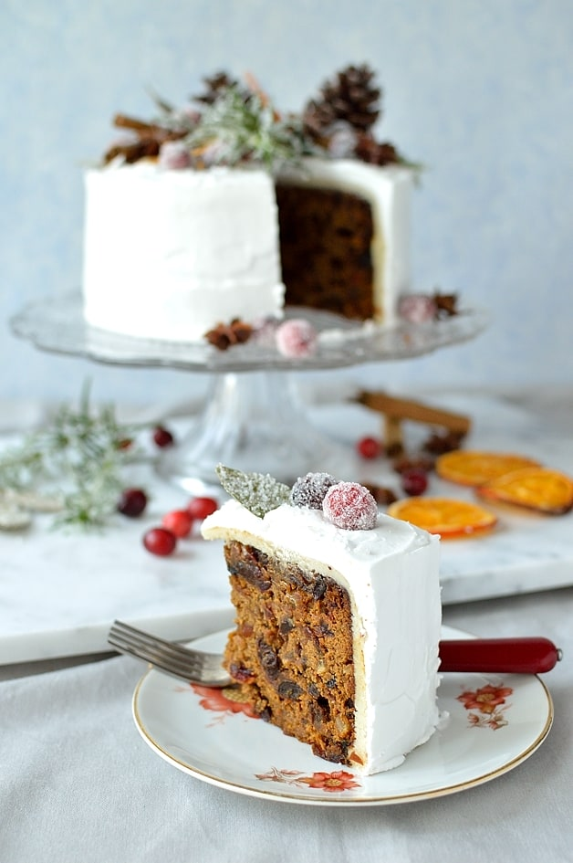 Moist ginger fruitcake topped with marzipan, royal icing, sugared cranberries, rosemary and bay leaves, dried orange slices, pine cones and whole spices - Domestic Gothess