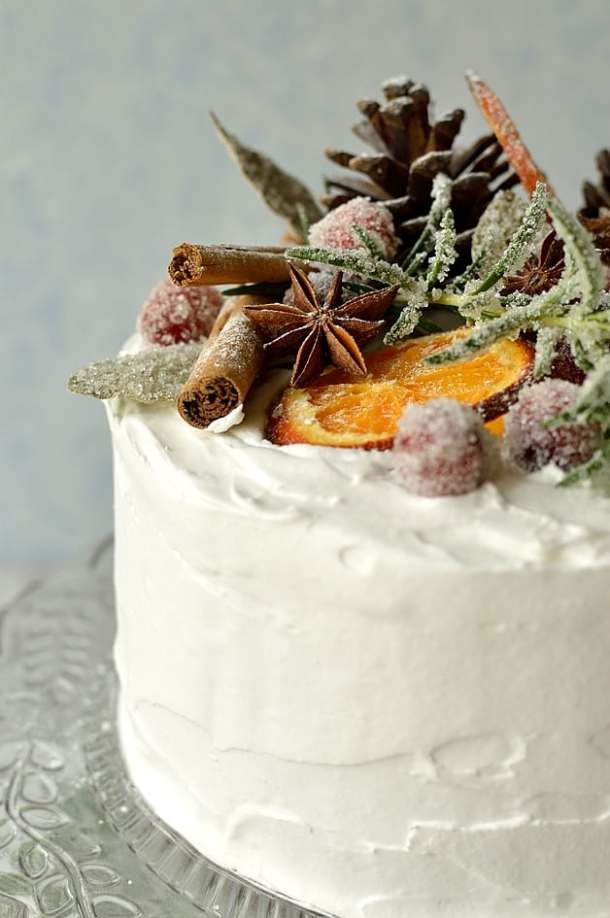 Moist, gingery fruitcake topped with marzipan, royal icing, sugared cranberries, rosemary and bay leaves, dried orange slices, pine cones and whole spices.