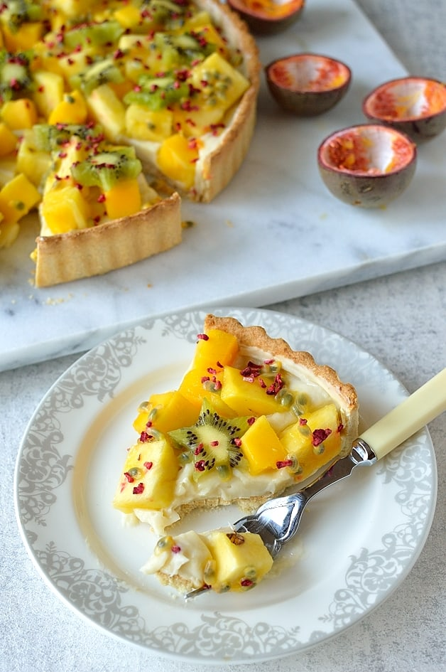 Tropical fruit coconut tart - crisp coconut pastry filled with coconut milk creme patissiere, mango, pineapple, kiwi & passion fruit