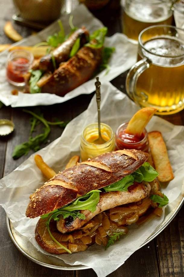 Sausages with beer pretzel hot dog buns, beer braised onions, rocket and roasted garlic butter - the perfect bbq food!