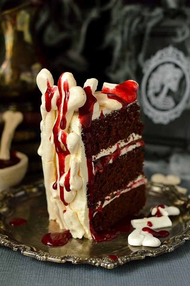 Meringue bone palace Halloween cake - moist chocolate cake filled with vanilla swiss meringue buttercream and raspberry jam covered in meringue bones with berry coulis 'blood' on the side
