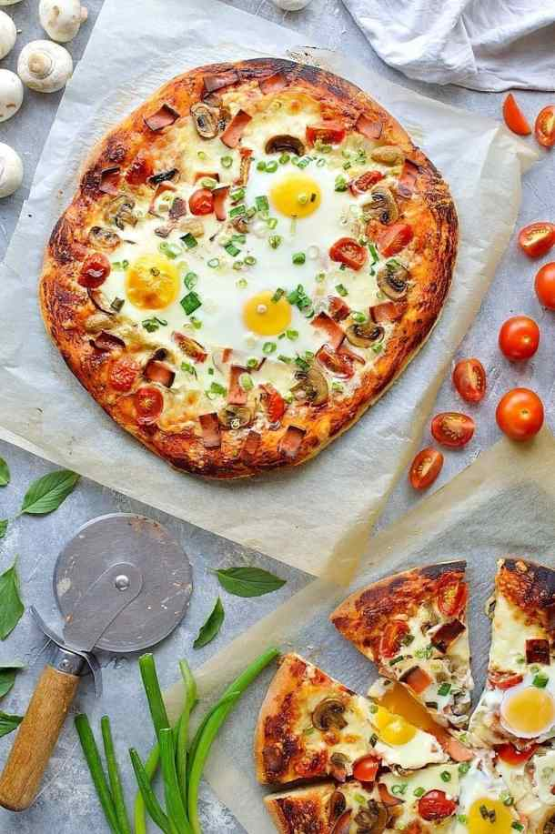 From above shot of breakfast pizza with tomatoes and basil