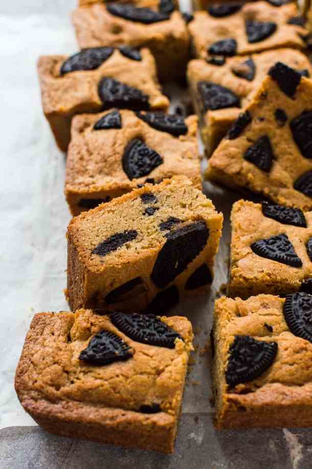 Angled shot of chewy peanut butter blondies filled with peanut butter Oreos.