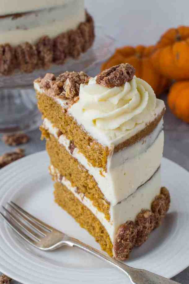 Close-up shot of a slice of pumpkin spice layer cake with mascarpone cream and sugared pecans.