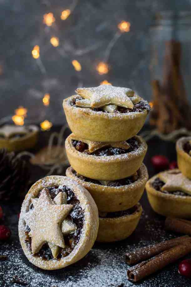 Photograph of a stack of lower calorie vegan mince pies with fairy lights in the background.