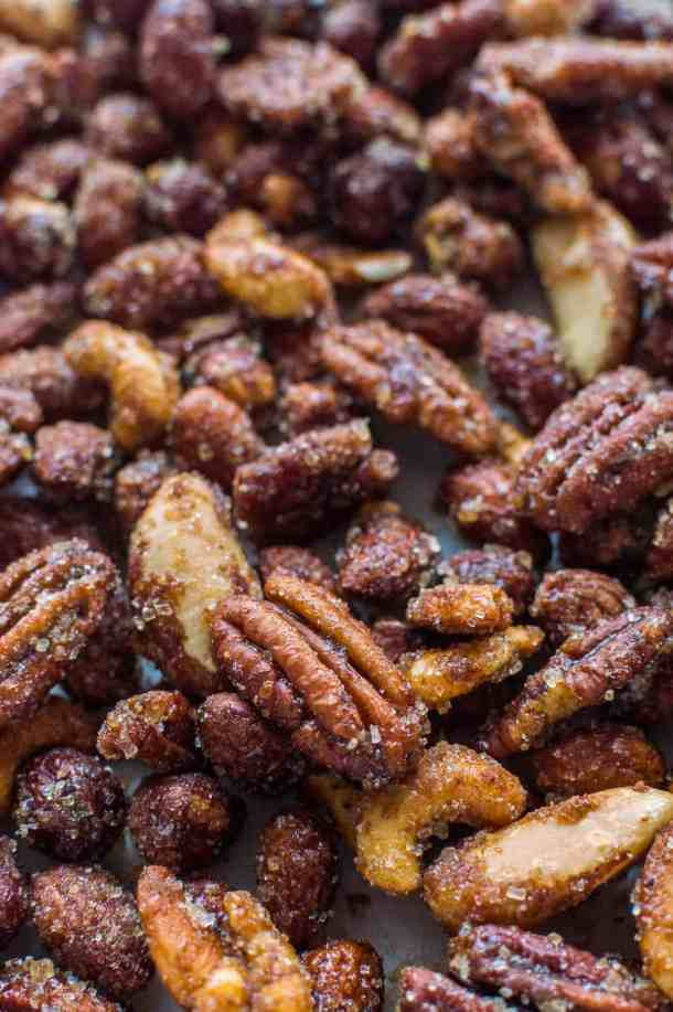 An angled shot of a tray of roasted, sugar coated pecans, cashews, almonds, hazelnuts and brazil nuts.