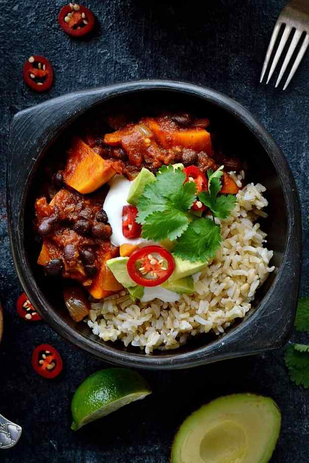 Sweet potato black bean chilli - a hearty, filling vegan meal. Serve with brown rice and all of the toppings!