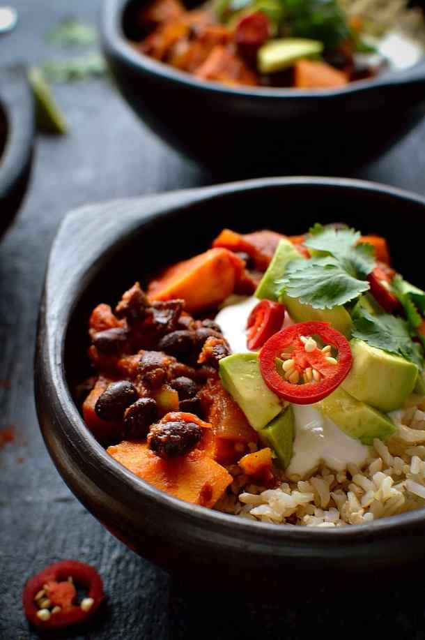 A close-up of sweet potato and black bean chilli in a black bowl served with brown rice, sour cream, avocado, red chilli and coriander.