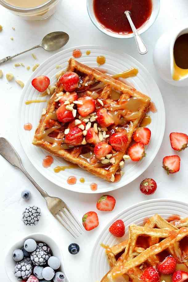 Peanut butter flavour square waffles topped with jam sauce, peanut butter sauce, strawberries and chopped peanuts.