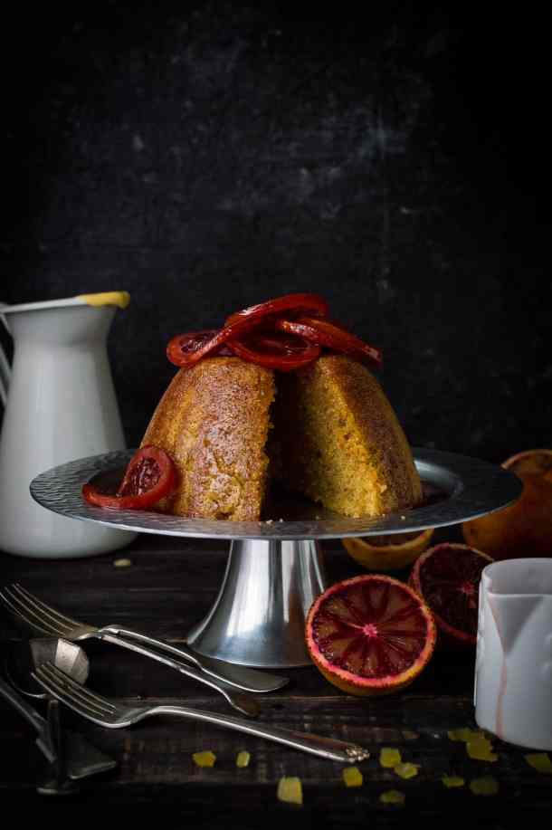 Sliced blood orange and ginger steamed pudding topped with candied blood orange slices on a silver cake stand