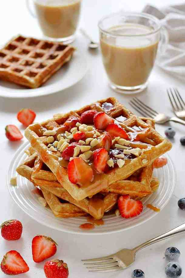 A stack of peanut butter and jelly waffles topped with strawberries and peanuts.