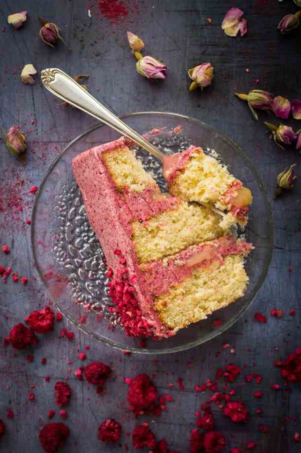A slice of three layered coconut cake with raspberry cooked flour frosting and lemon curd.