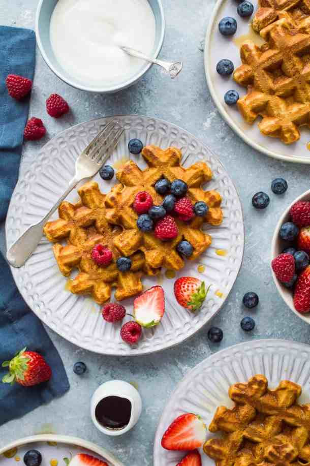 Three plates of spiced sweet potato waffles with maple syrup and berries on a grey background.