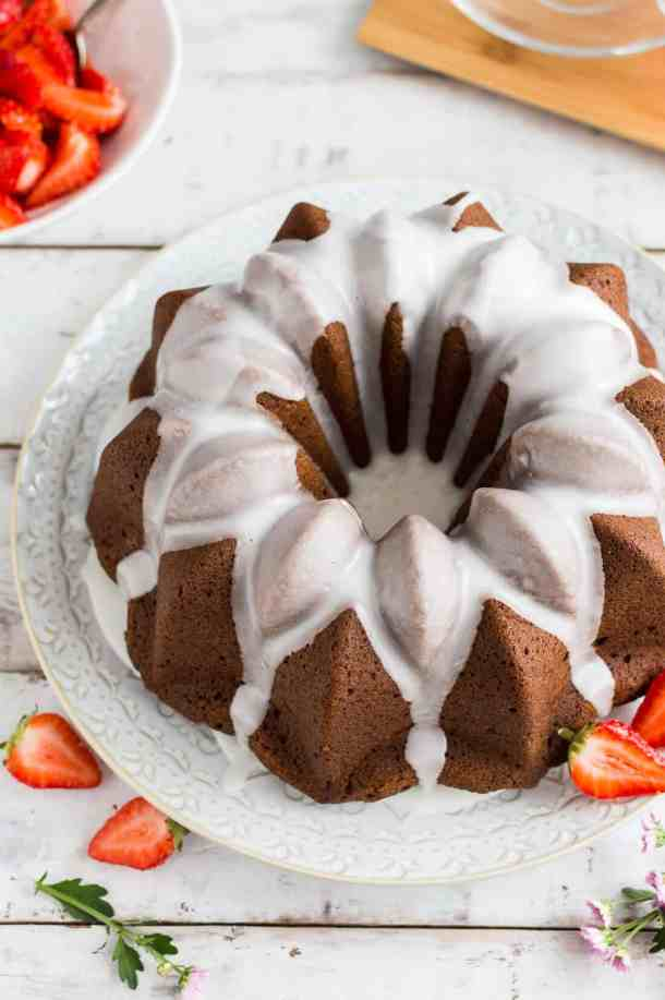 Side shot of vegan ginger bundt cake topped with a lime glaze and served with macerated strawberries.