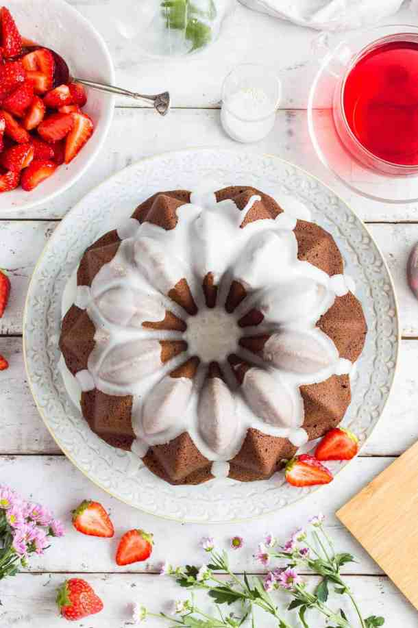 Vegan ginger bundt cake with lime glaze and macerated strawberries – a moist, spicy, easy to make cake served with juicy strawberries; perfect for afternoon tea! #gingerbread #vegan #vegancake #veganbaking #dairyfree #eggfree #bundtcake