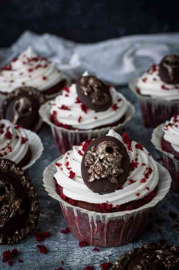 Vegan red velvet cupcakes topped with chocolate skull cameos for Halloween.