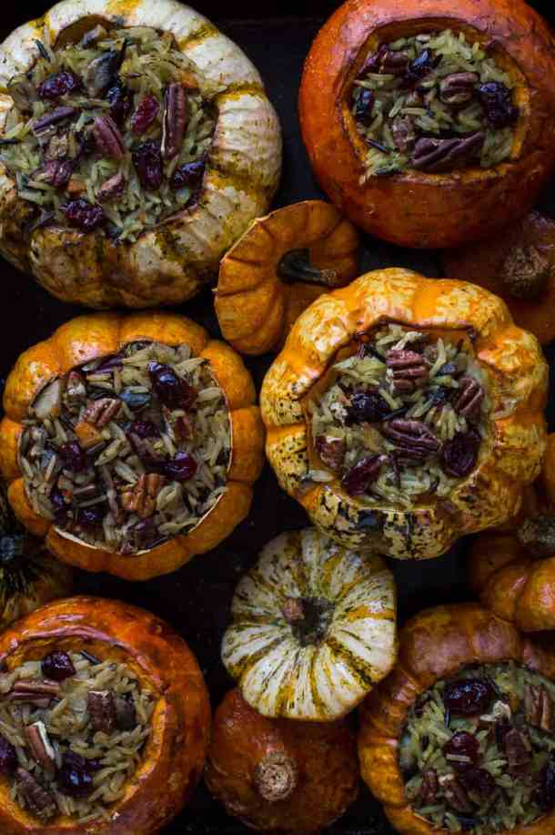 Roasted mini pumpkins and squash filled with cranberry and pecan vegetable wild rice in a roasting tray.