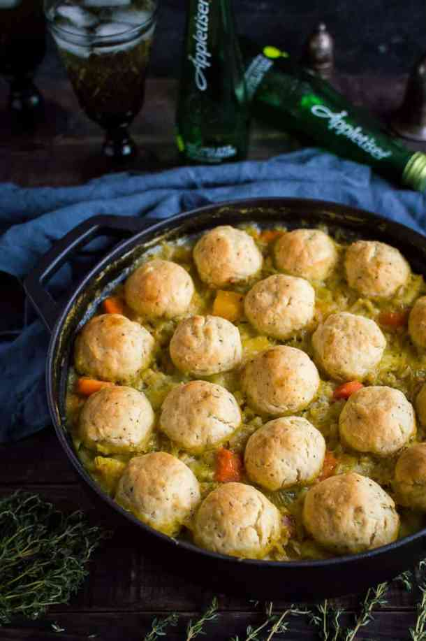 Vegan vegetable and pearl barley stew topped with herby dumplings in a cast iron pan with Appletiser in the background.