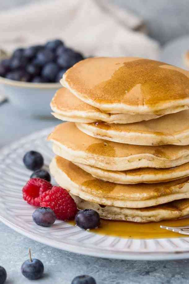 Close up of a stack of fluffy vegan vanilla pancakes with maple syrup and fresh berries on a white plate.