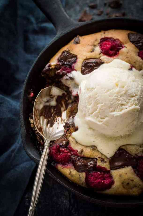 Close up of vegan chocolate raspberry skillet cookie topped with vanilla ice cream with a spoonful removed.