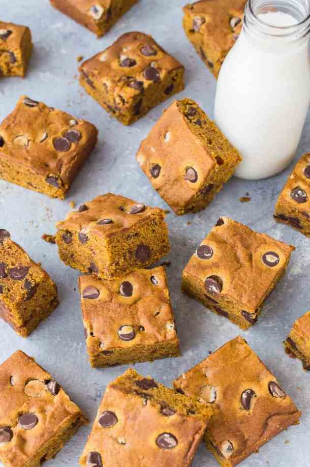 Vegan chocolate chip pumpkin cake bars on a grey background with a bottle of almond milk.