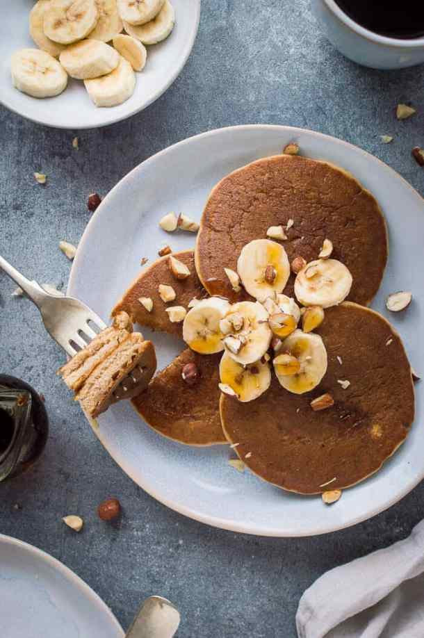 A plate of three fluffy vegan banana pancakes topped with sliced banana, hazelnuts and maple syrup with a forkful taken out on a grey background.