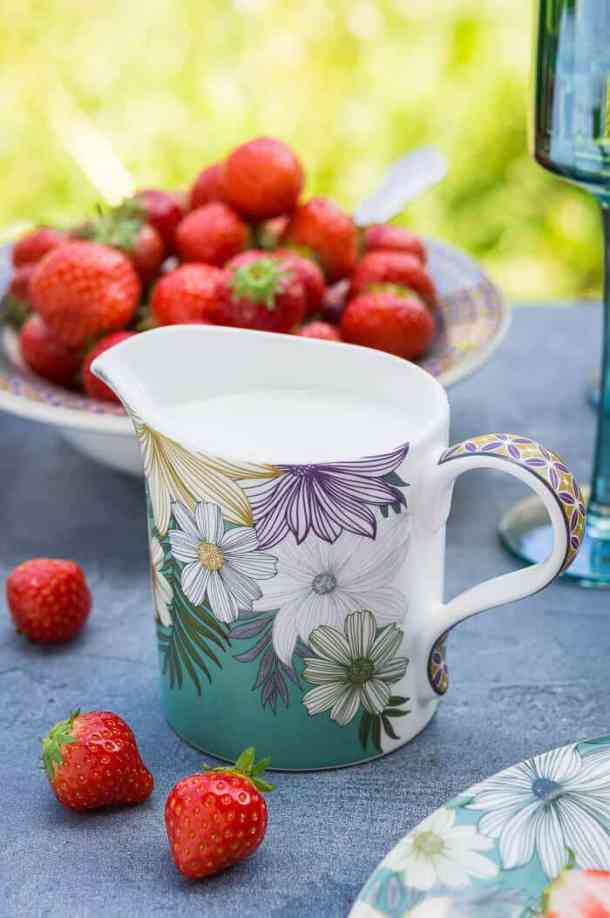 A floral patterned jug full of cream with a bowl of strawberries.