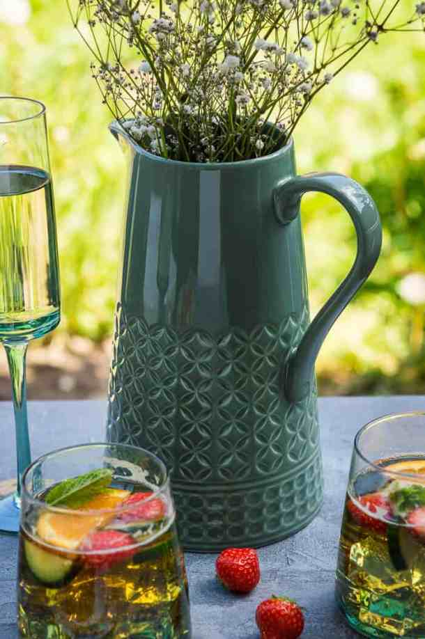 A large embossed green jug with flowers in it.
