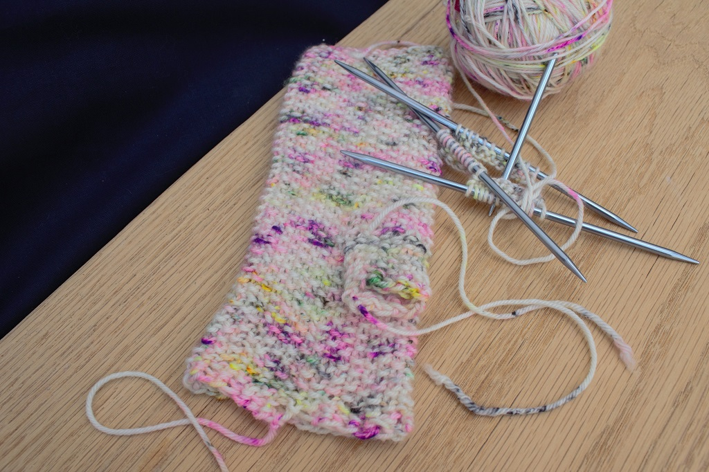 One finished knitted fingerless mitten and one just cast on.
