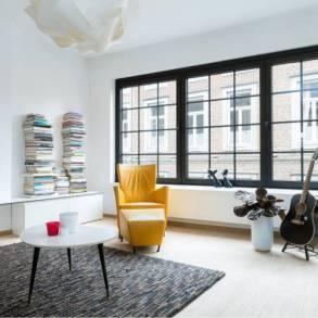 salon, gitara, żółty fotel, dywan, książki ułożone w stosie,