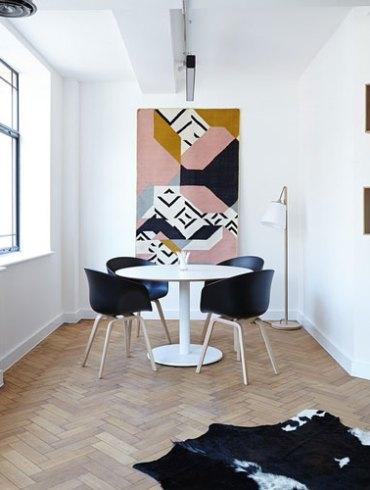Designerskie czarne krzesła i biały okrągły stolik w małym salonie.