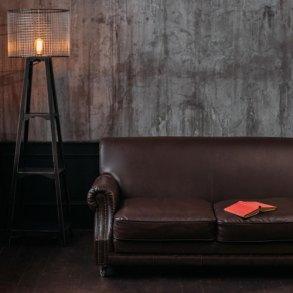 Ciemne wnętrze z betonową ścianą. Na jej tle znajduje się sofa dwuosobowa oraz lampa stojąca.