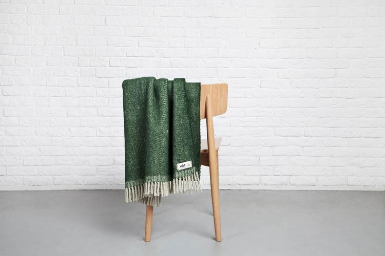 Zielony koc powieszony na drewnianym krześle
