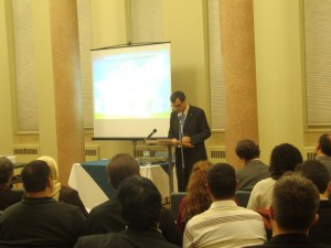 Dr. Claudio Monge speaks to an eager audience while a projector screen stands behind him.