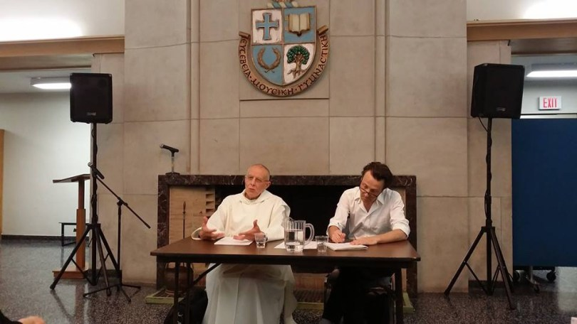 Jacques Dupont, a Carthusian Monk, sits and speaks while another man takes notes.