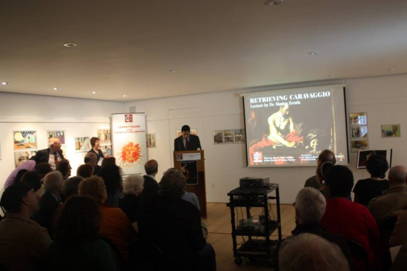 "Picture shows an audience, a podium and a projector screen. The screen says ""Retrieving Caravaggio lecture by Dr. Marius Zerafa."""