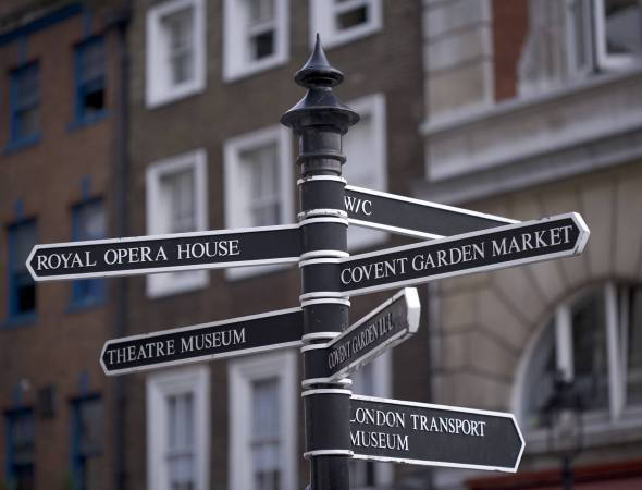 England, London, Covent Garden, black and white signpost with directions to Covent Garden Market, the Royal Opera House and various museums.