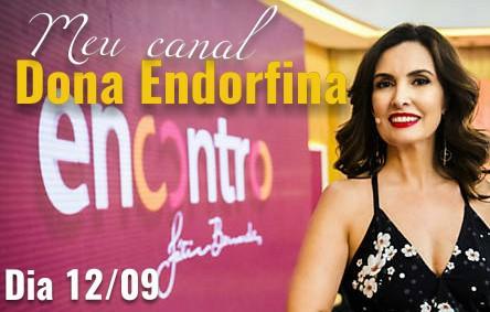 pracego: Fatima Bernardes ao lado do banner Programa Encontro com o texto Meu Canal Dona Endorfina no Encontro com Fátima Bernardes
