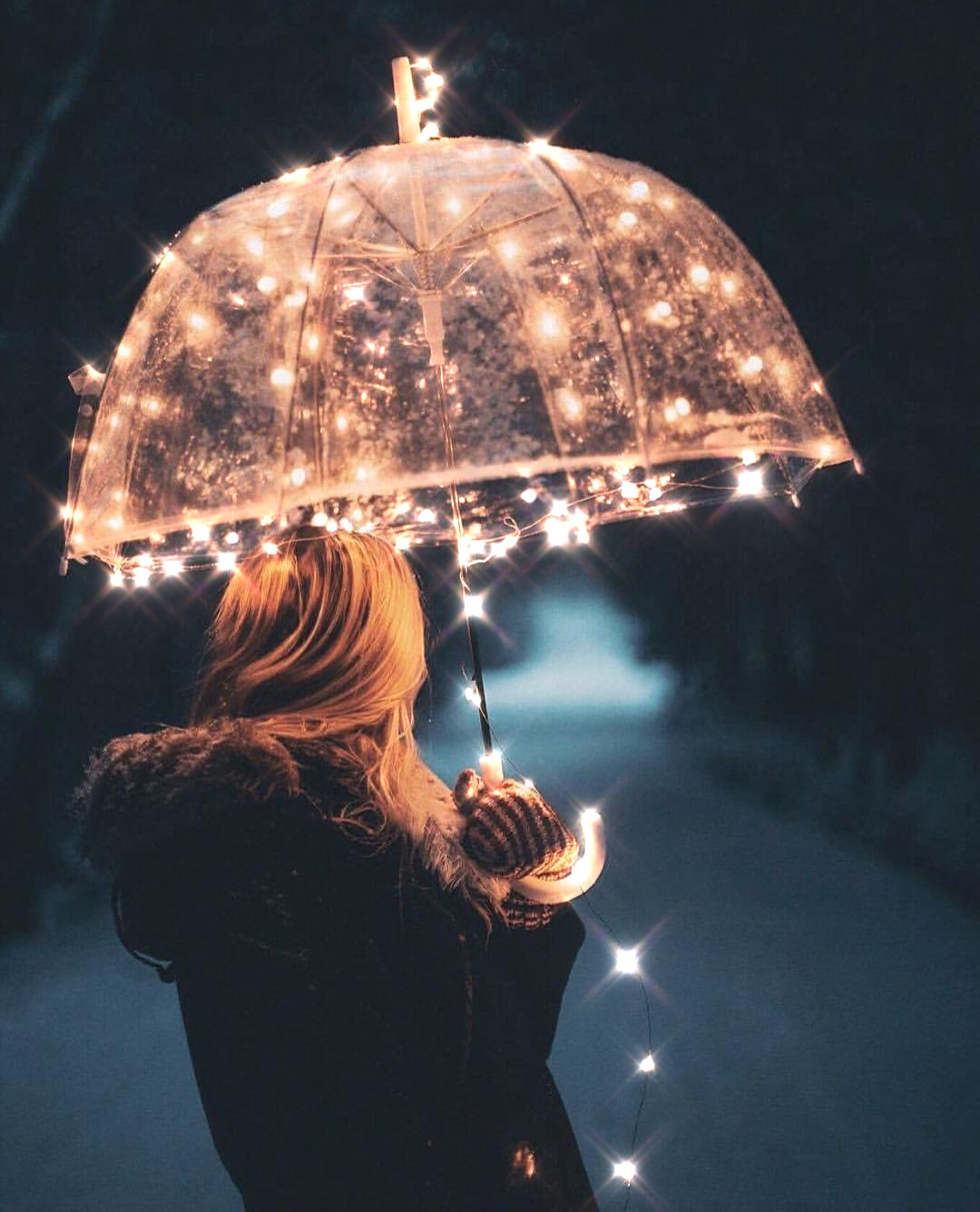 Woman holding umbrella with lights