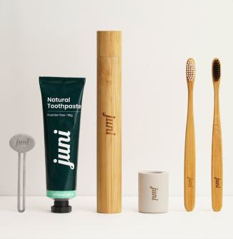 The Juni Essentials starter kit features a metal toothpaste wringer, a natural toothpaste with recyclable tubing, a bamboo toothbrush travel case, a toothbrush holder, and two bamboo toothbrushes - one with white colored bristles and one with charcoal colored bristles