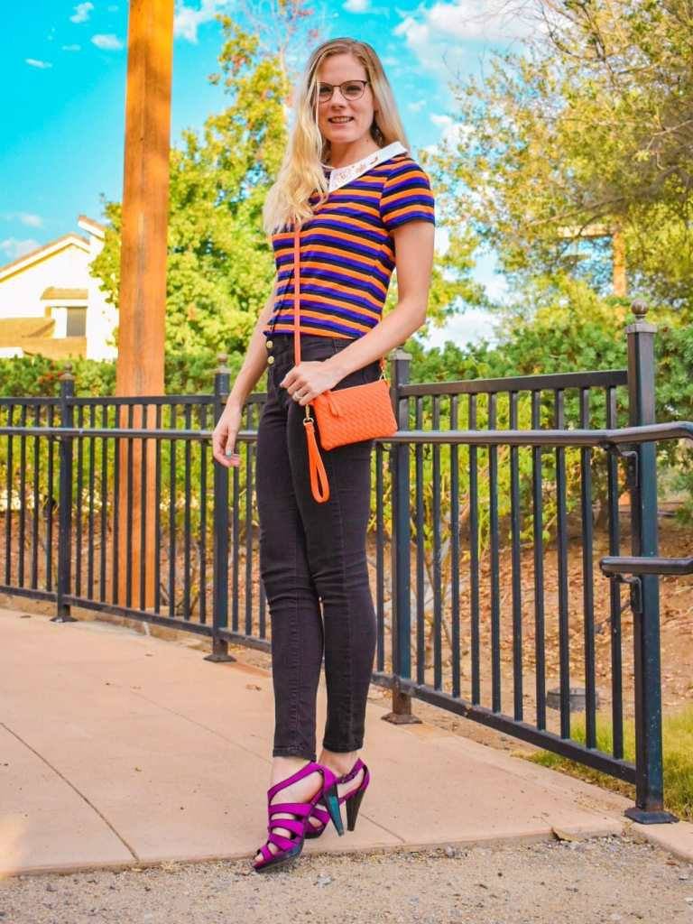 Posing on a sidewalk in fall, I am showing how the whole outfit came together. The crop top has a white collar, and black, purple, and orange stripes. The orange in the shirt was matched to the bag I have. And the purple of the shirt was matched to my heels. Both of these two pops of color really help to show that the crop top is the center of attention!