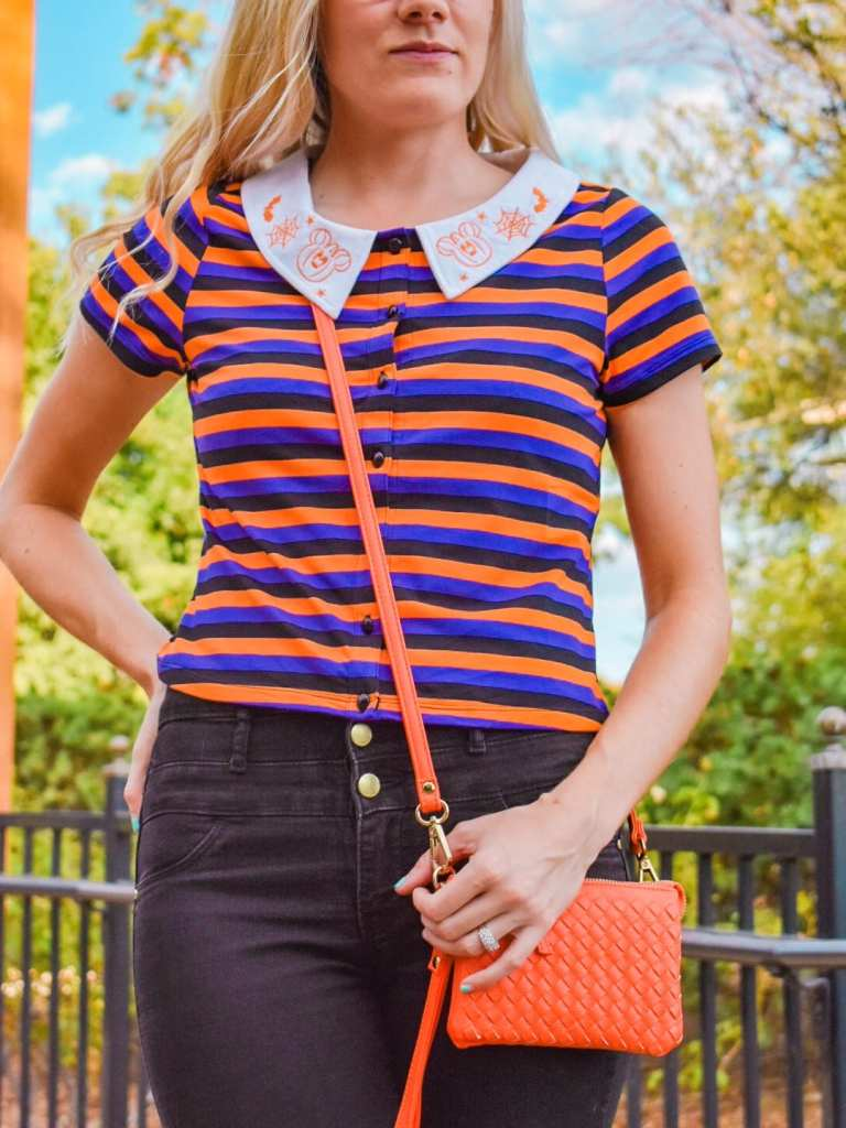 A detail picture of my outfit featuring the accent colors to match the Disney Halloween style crop top from Her Universe. You can see better how the shirt fits and wear it lands on my waistline. You can also see the embroidery of the collar matches the orange of my crossbody bag perfectly!