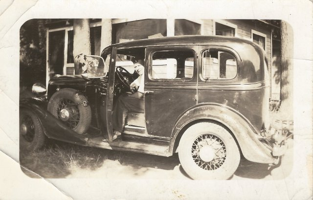 Photo of a man in a vintage auto.