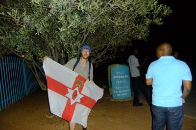 Jonny Blair and the travelling Northern Ireland flag in Botswana at Tlokweng