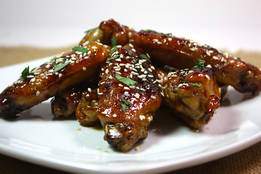 honey Sriracha wings stacked on white plate garnished with sesame seeds and cilantro