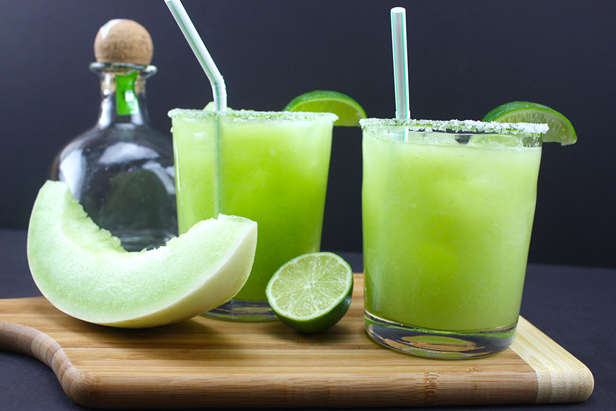 honeydew margaritas in two clear glasses garnished with lime wedges on wooden board