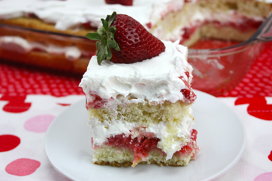 slice of strawberry shortcake on white plate with whole cake in background